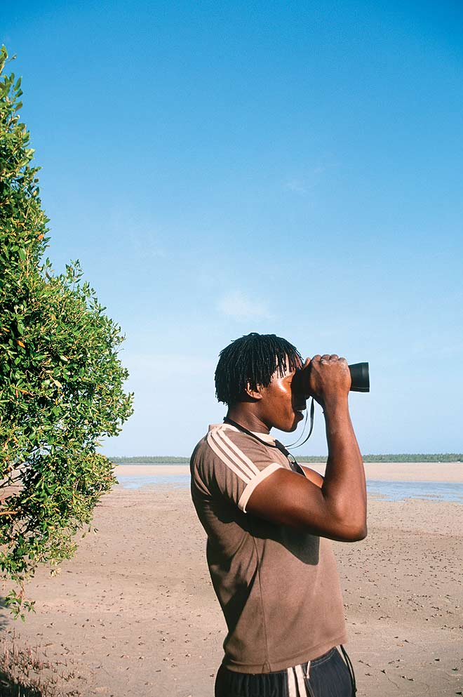 A man looks through binoculars at Turtle Bay. Marine conservation organisations are educating fishermen to protect the biosphere of East Africa