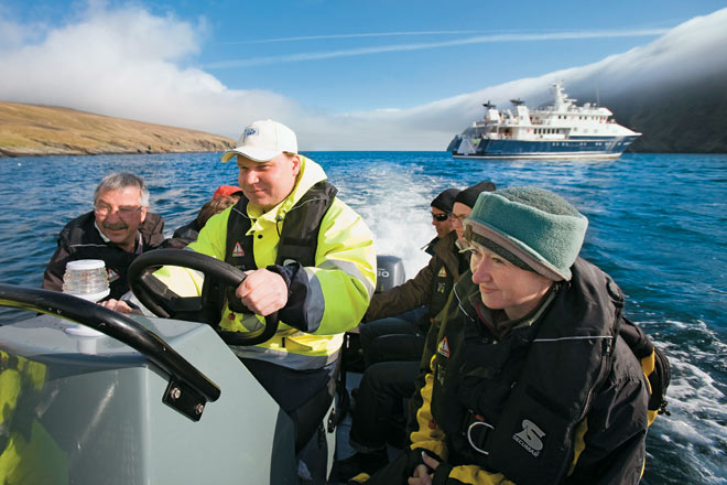 A ferryman takes visitors for a ride on his inflatable rubber boat, in the waters off Unst