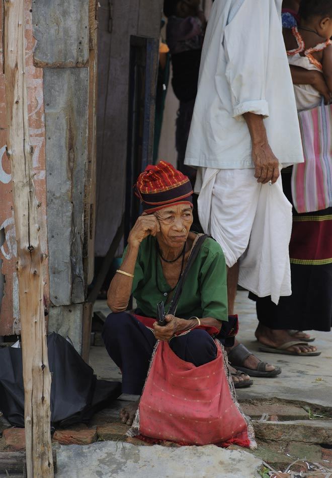 A Tripuri tribal lady waits at a bus stop on the road to Kailashahar