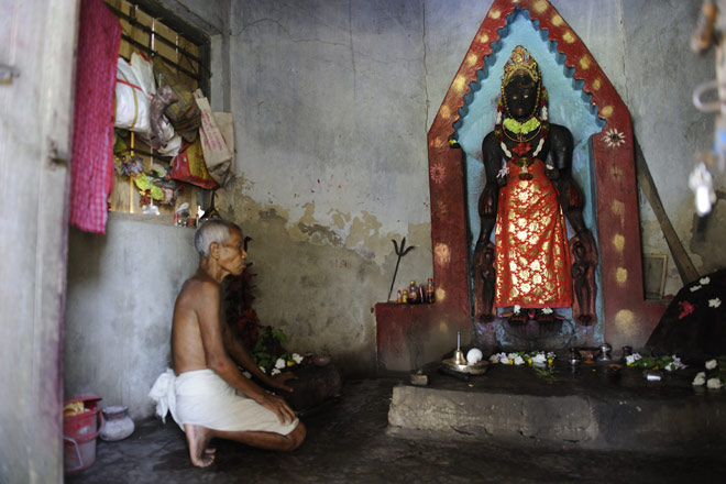 An ancient statue of the Bodhisattva Avalokiteshvara being worshipped as Kali by an old shaman in the village of Kalma
